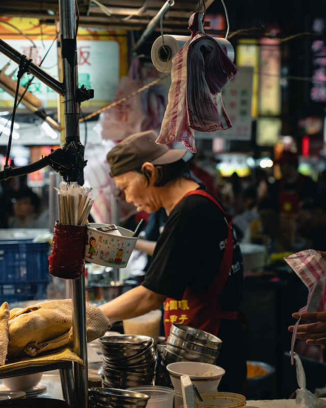 An aproned man prepares bowls of noodles from a stall at Ningxia St. Night Market in Taipei