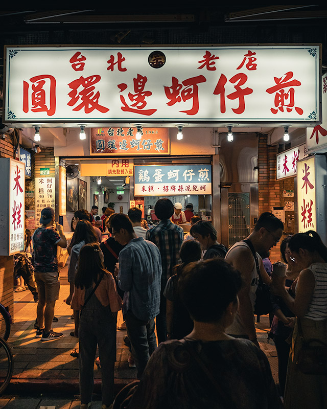 A queue of people wait outside the neon lit exterior of Yuan Huan Pien, a Michelin Guide recommended oyster omelette restaurant at Ningxia St. Night Market in Taipei
