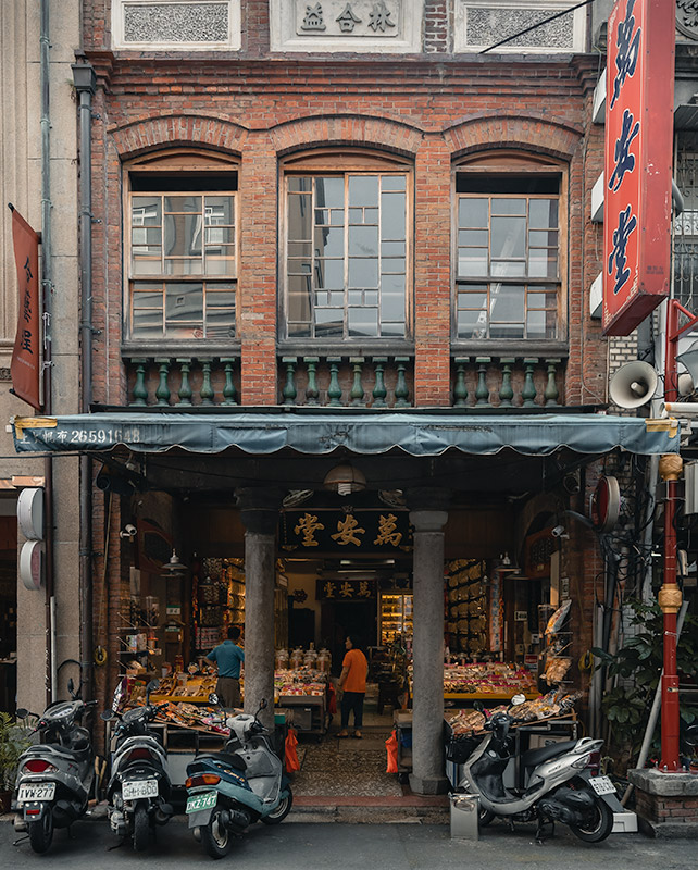 An old brick facade with an open shopfront and motorbikes parked outside in Dadaocheng, Taipei's oldest neighbourhood