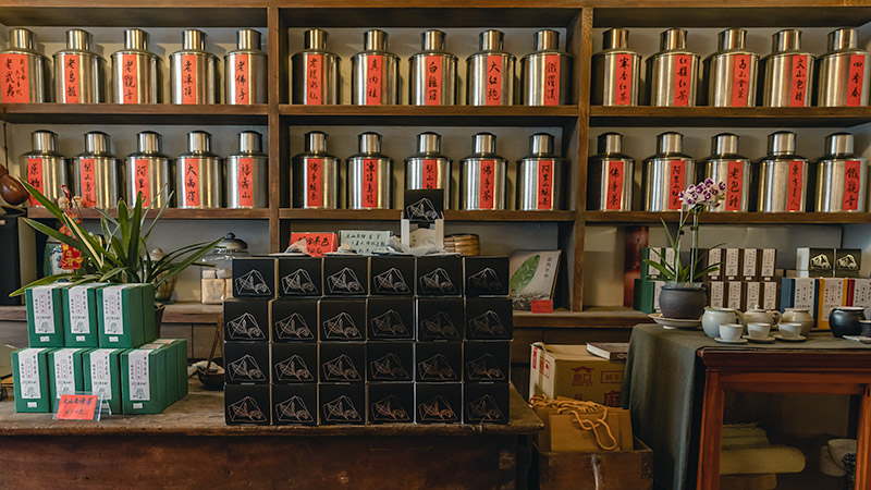 Rows of tea displayed in metal urns on old wooden shelving in a traditional tea store in Dadaocheng, Taipei's oldest neighbourhood