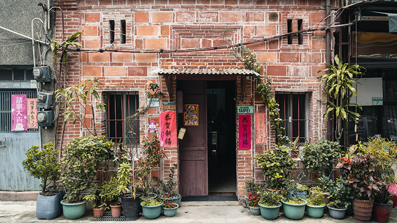 A red sandy brick facade surrounded by countless potted plants in Dadaocheng, Taipei's oldest neighbourhood