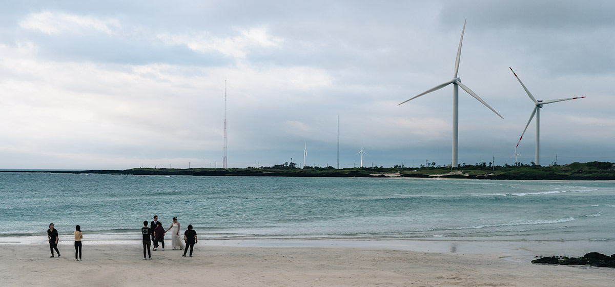 A couple pose for wedding shots on Gimnyeong Beach as two massive wind turbines spin on the headland behind them.