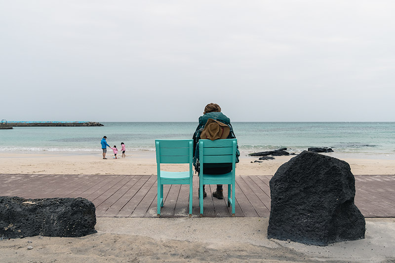 A person sits on a cute green chair facing Woljeong Beach on Jeju.