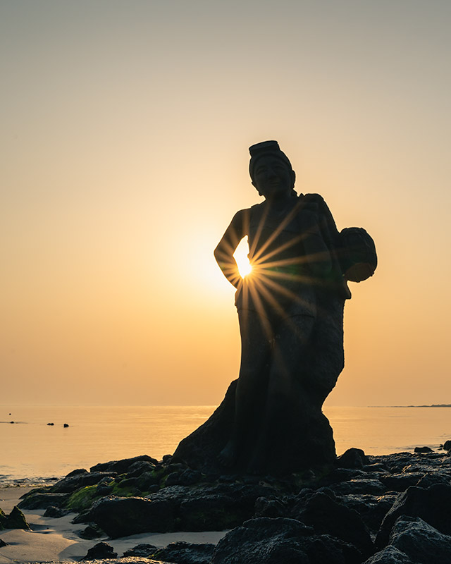 A tall statue of a women free diver with the sun bursting between the crook of her arm. An image from one of the best beaches on Jeju Island, Hagosudong Beach.