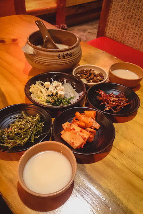 The side dishes and a bowl of dong dong ju at the authentic Cheontaemansang in Tongyeong