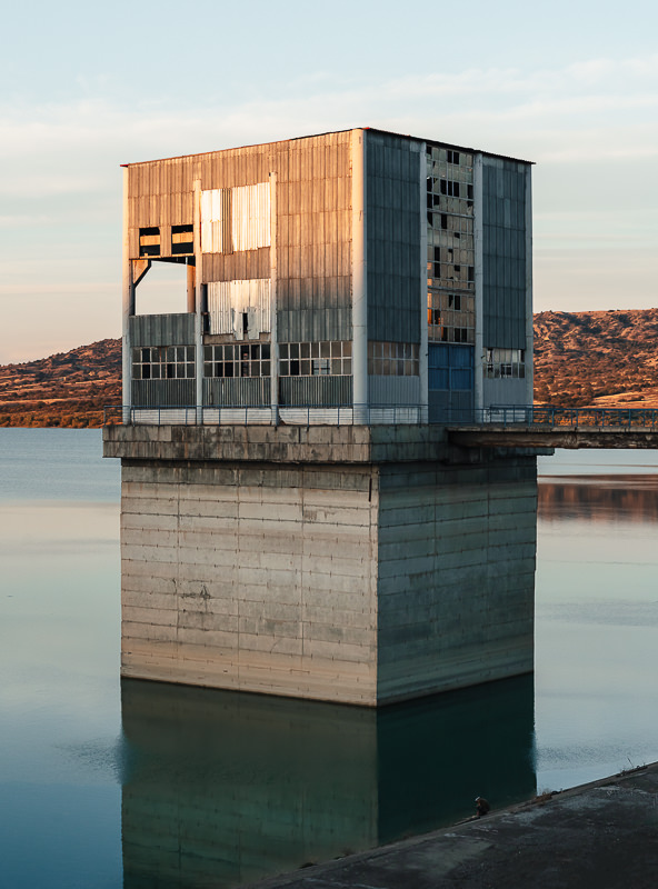 Glowing orange from the setting sun, a seemingly abandoned blocky building rises from the water at the edge of the Dali Mta Reservoir in Georgia
