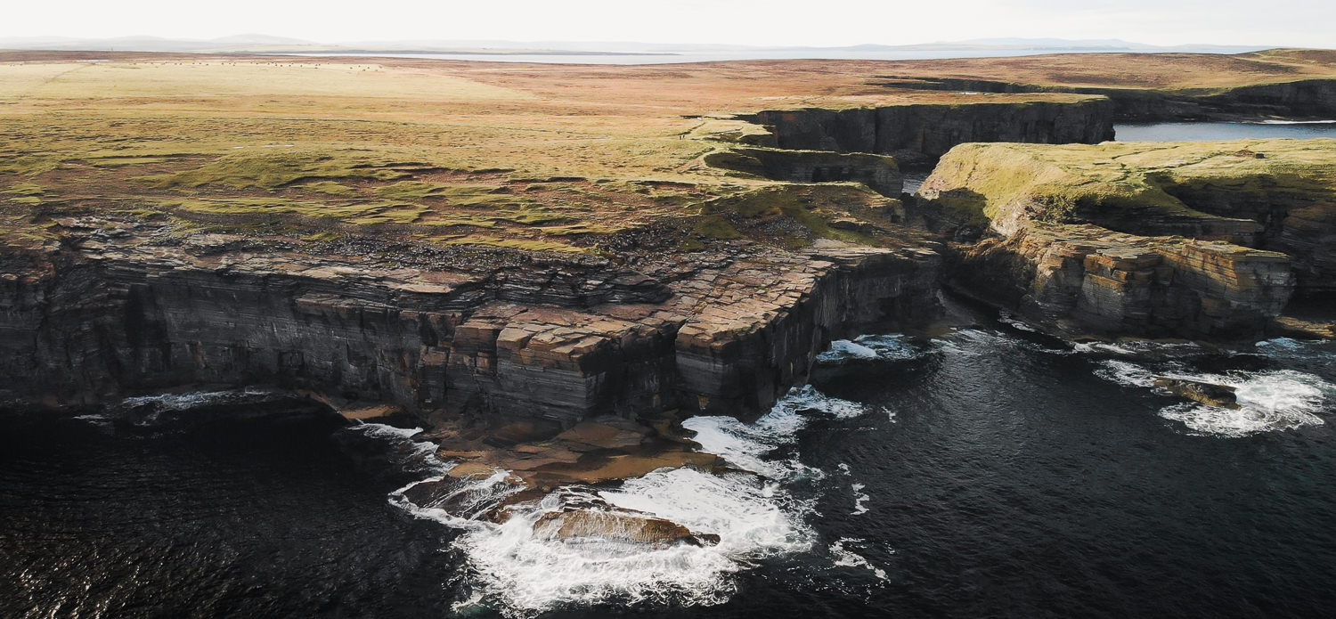 An aerial view of the the cliffs along the Deerness coast on Orkney Mainland, with waves crashing into the rocks below