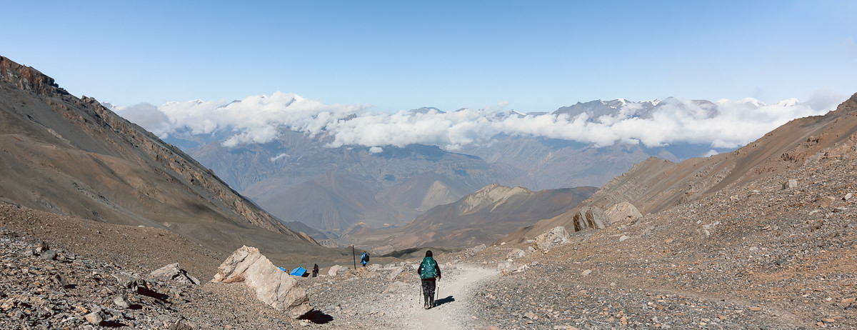 A trekker descending the trail from Thorong La on the Annapurna Circuit