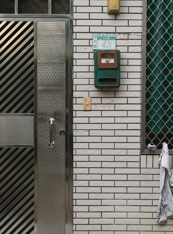 Detail shot of a facade in a Tainan alley, with tiles, letterbox and patterened window and door grates
