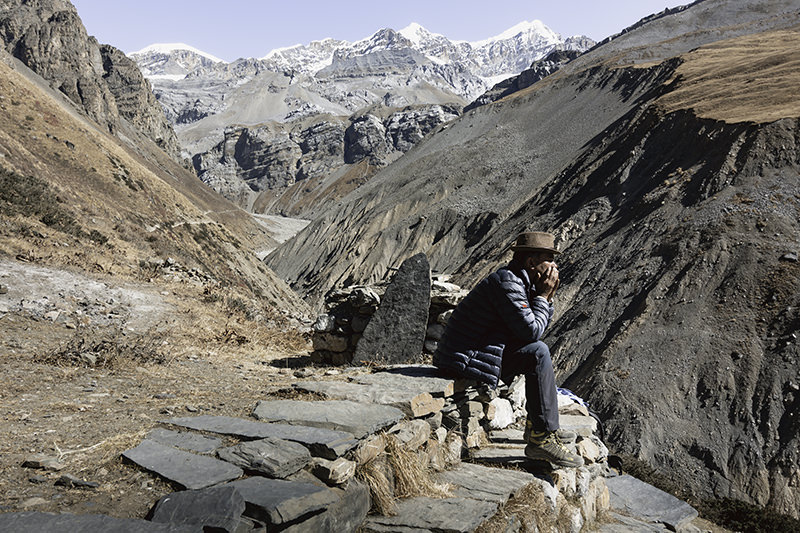 A trekker taking a break on a rocky wall, looking out at the view from Deurali Teahouse