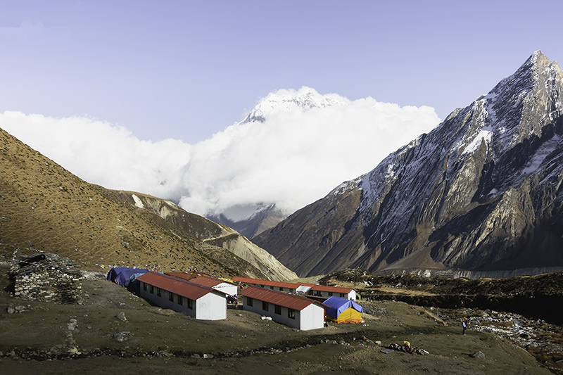 Red roofed trekking lodges shining in the afternoon sun at Dharamsala on the Manaslu Circuit