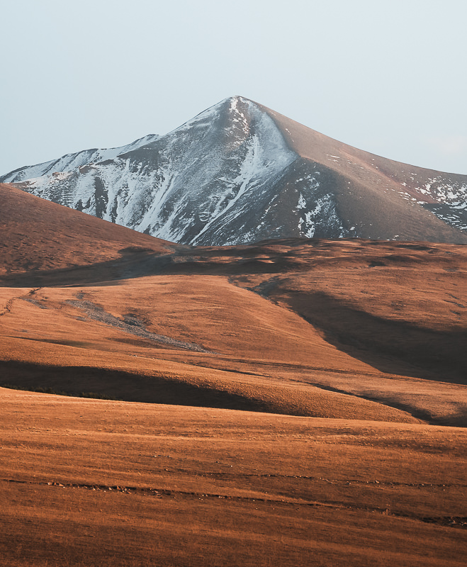 The pointed, snow dusted peak of Didi Abuli stands above golden slopes at sunset on the Javakheti Plateau
