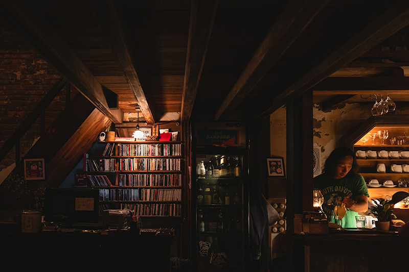Behind the bar at Lola in Tainan. A barman prepares a cocktail next to a bottle cooler and a shelf of cds, surrounded by dark wood and soft yellow light
