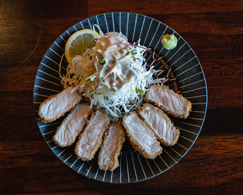 A top-down photo of a plate with pieces of pork cutlet arranged in a circle around a cabbage salad