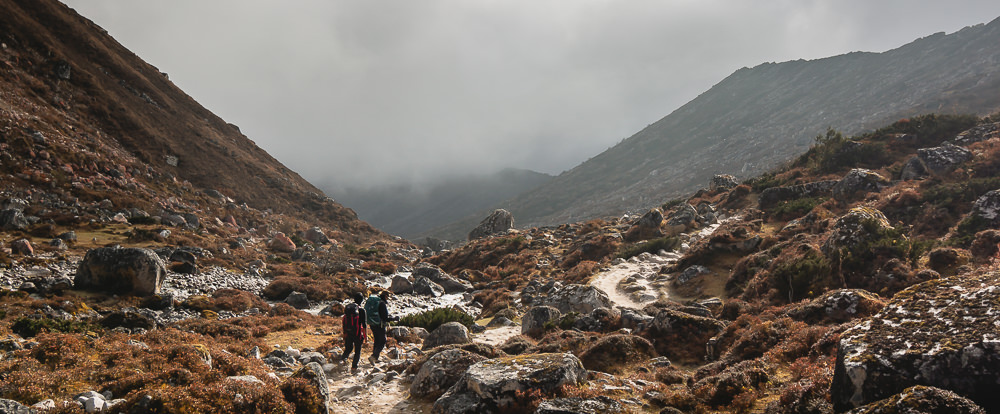 Two hikers descend towards Bimthang in cloud and sunshine through a landsacpe of rocks and bushes
