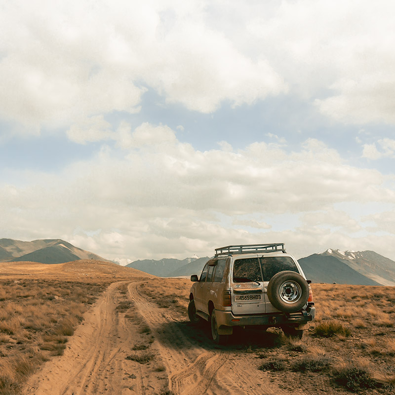 A Toyota Landcruiser is parked on the side of a sandy track in the Zorkul Nature Reserve in Tajikistan while on a Pamir Highway Road Trip