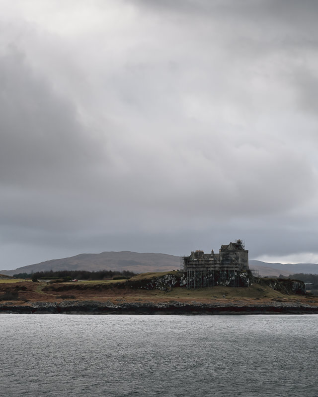 Duart Castle covered in scaffolding beneath leaden skies, seen from the ferry between Mull and mainland Scotland.