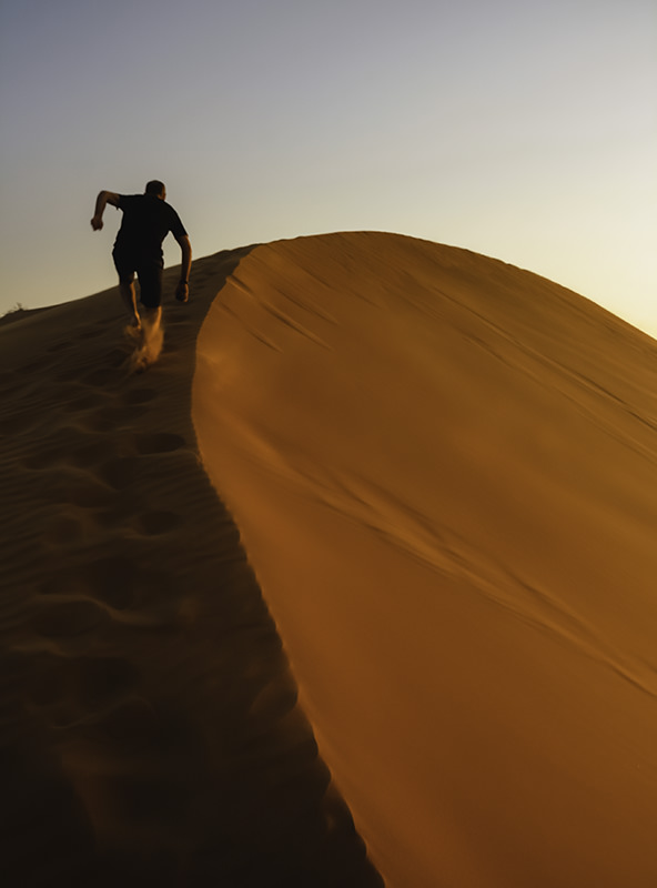 A figure runs up a red sand dune at sunset in Wahiba Sands, Oman