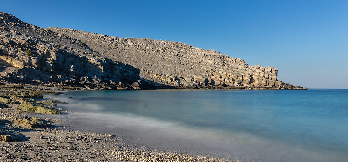 Striking rock formations and brilliant blue seas at Rocky Beach in Musandam, Oman