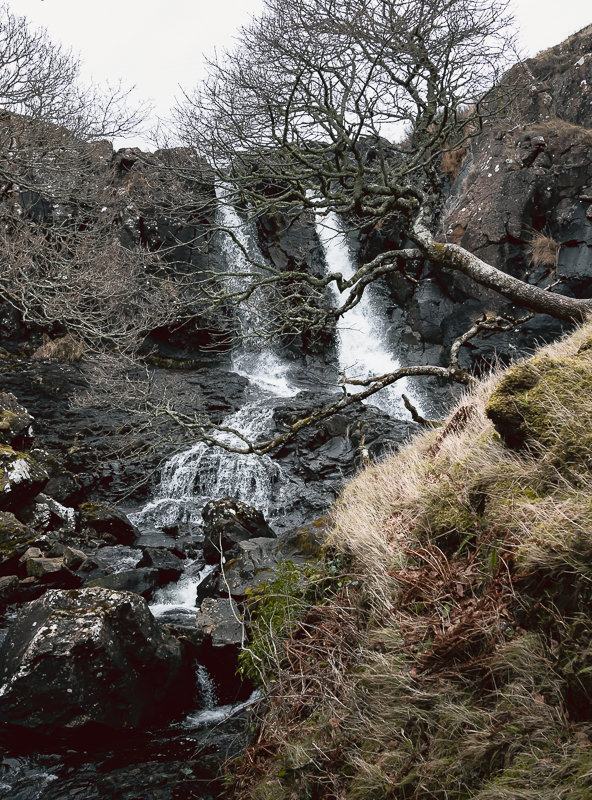 Eas Fors Waterfall tumbling from the ciffs above the road on the Isle of Mull in Scotland.