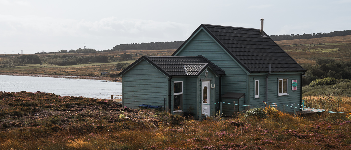 A small and cute wooden building (Emily's Tea Room) among the rust coloured grasses and heather, close to the shore on the east coast of Hoy