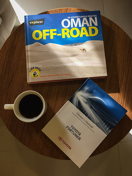 A copy of an Oman Off-road book and a vehicle manual - a must for any Oman camping road trip