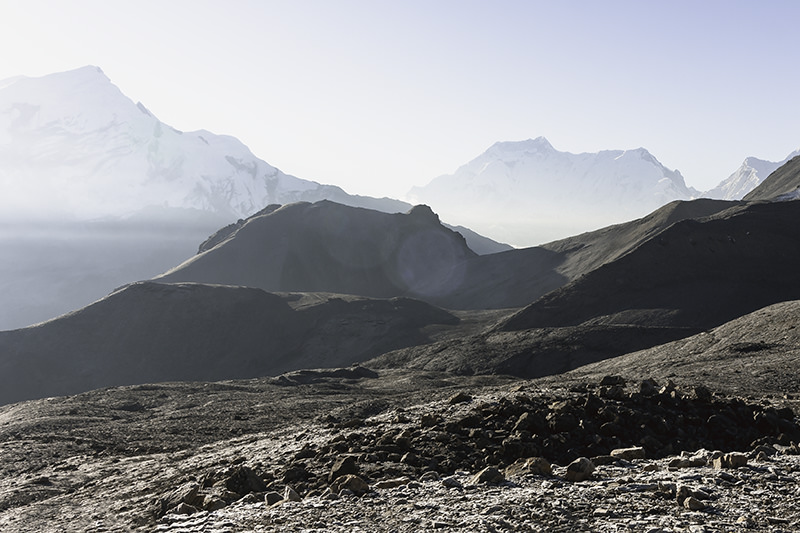 Dry rocky mountains, and a backdrop of snow covered peaks at sunrise on the approach to Thorong La