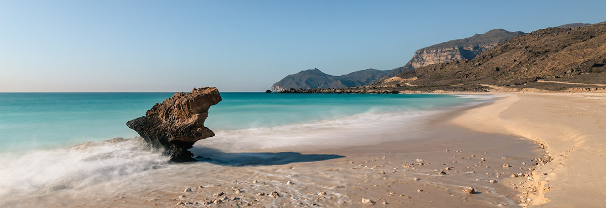Golden sand and turquoise water at Fazayah Beaches in Oman, a distinctive low sea stack poking from the water