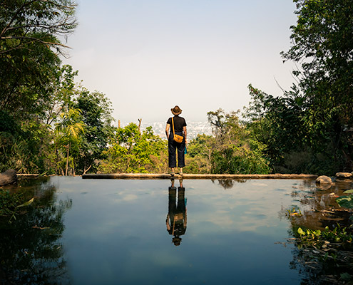 Looking out from wat Pha Lat over Chiang Mai, reflected in the still water and surrounded by lush green vegetation