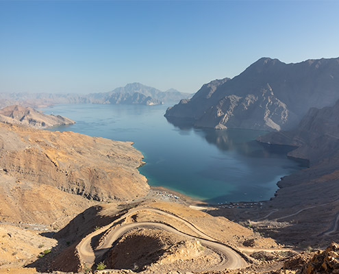 The mirror-like blue surface of Khor Najd stretches into the distance, framed by sandy mountains and cliffs