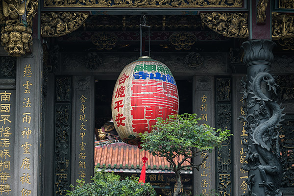 A boldly coloured huge lantern hangs at the entrance to Longshan Temple, Taipei