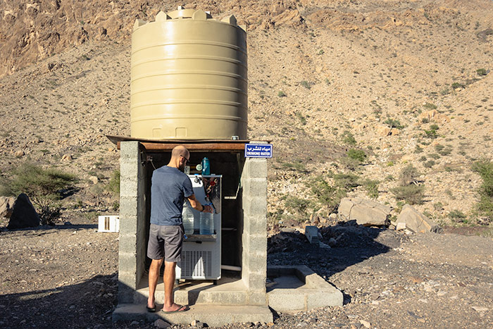 Filling up drinkable water in the mountains of Oman from a large cistern and dispenser