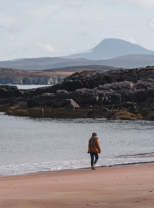 A lone figure walks along the shore at Firemore Beach with distant mountain views in the background