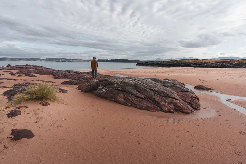 Richly coloured orange red sand and eye-pleasing rock formations stretching up Firemore Beach, an easy side trip from the North Coast 500 route in Scotland