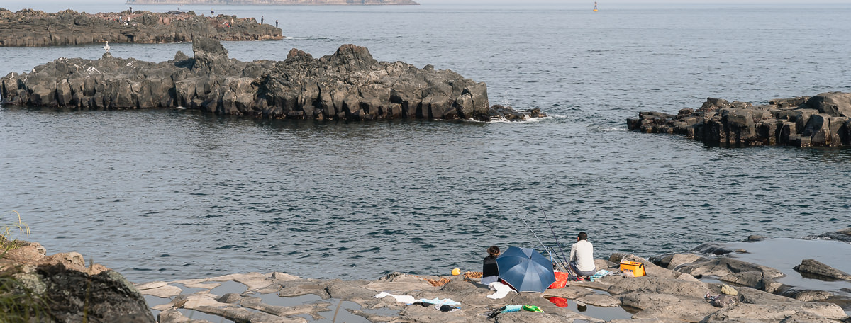 A couple are fishing on the rocks at Gangjeon-cheon, where the river meets the sea