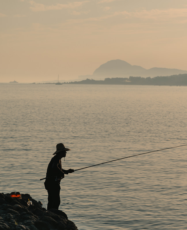 A lone fisherman stands on the rocky shore, fishing at sunset near Wolpyeong Port