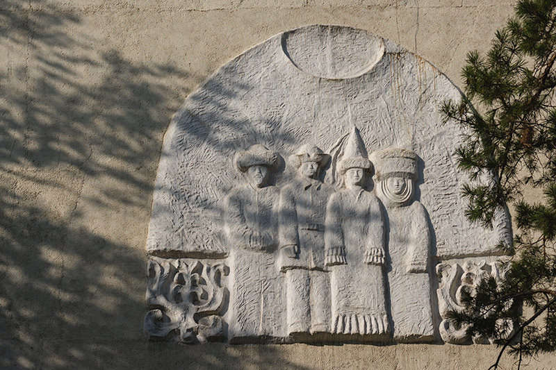 Frieze of men and women in traditional Kyrgyz dress on a building near Panfilov Park