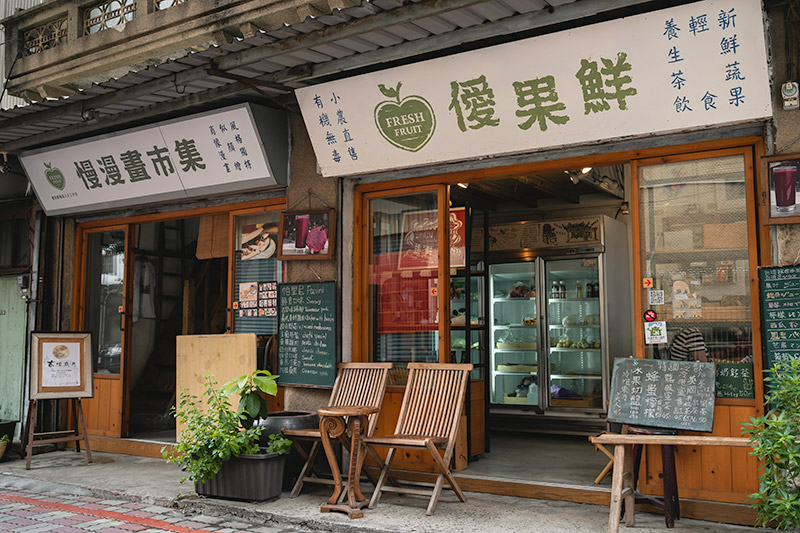 The entrance to the fresh fruit juice cafe in Tainan, with wooden chairs and plants outside