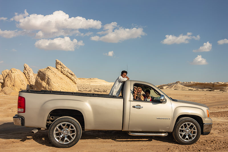 An elederly gent and his grandsons pose for photos from their 4WD on the sandy coast of Eastern Oman