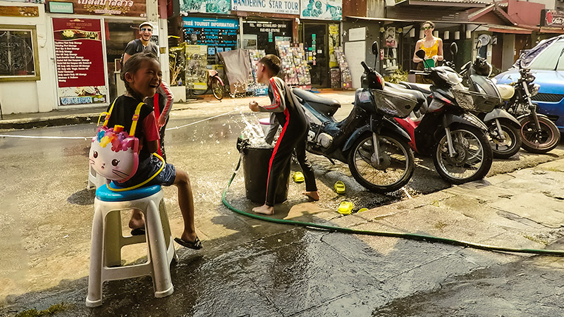 Local kids having a waterfight with tourists at the side of the street at the Songkran Festival in Chiang Mai, Thailand