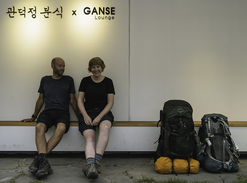 Two weary hikers rest outside the Ganse Lounge in Jeju City after a month hiking on the Olle Trail