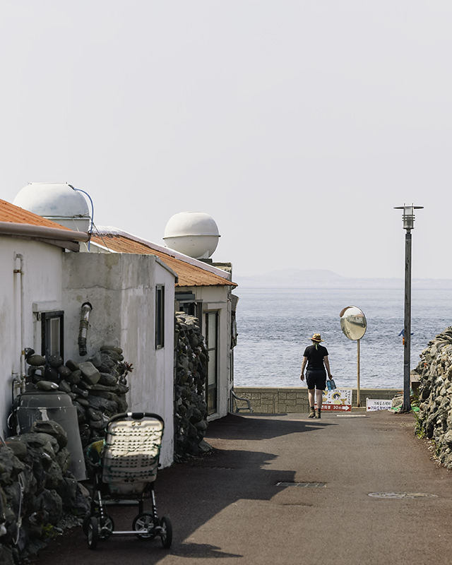 A person returns to the coast through the low traditional houses and lanes on Gapa-do