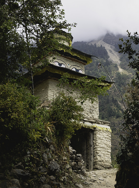A tall stone gate with painted eyes on the Manaslu Circuit Trek