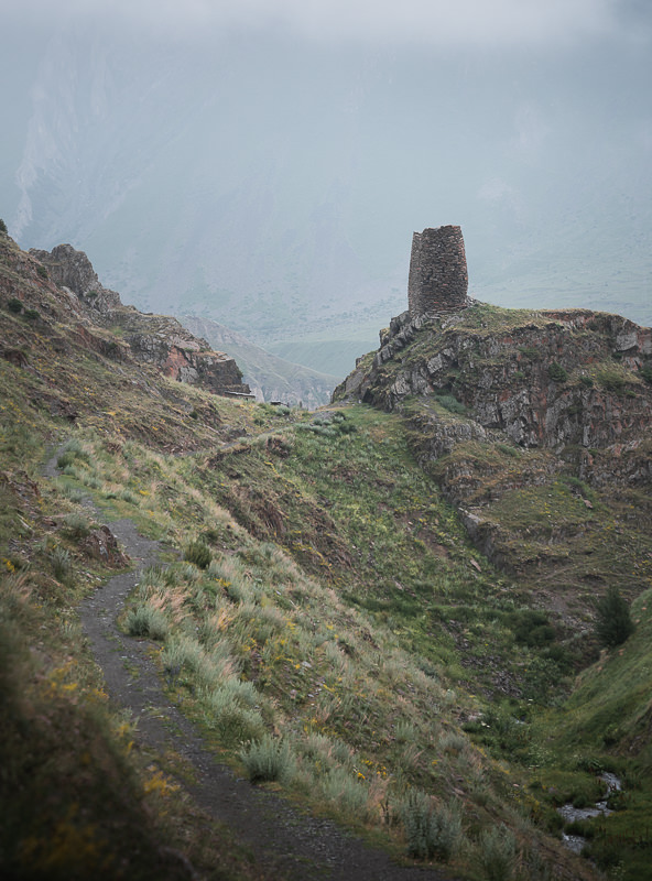 An old watchtower sits next to the trail on the hiking path to Gergeti Trinity Church in Kazbegi, Georgia