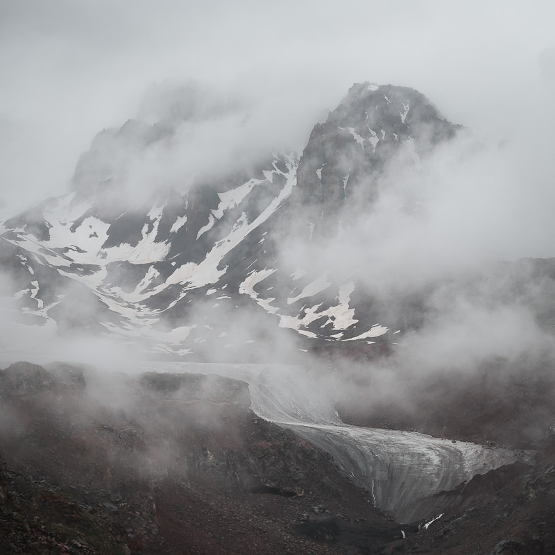 A view through the mist of Gergeti Glacier and the mountains behind, seen from the hiking trail above Altihut