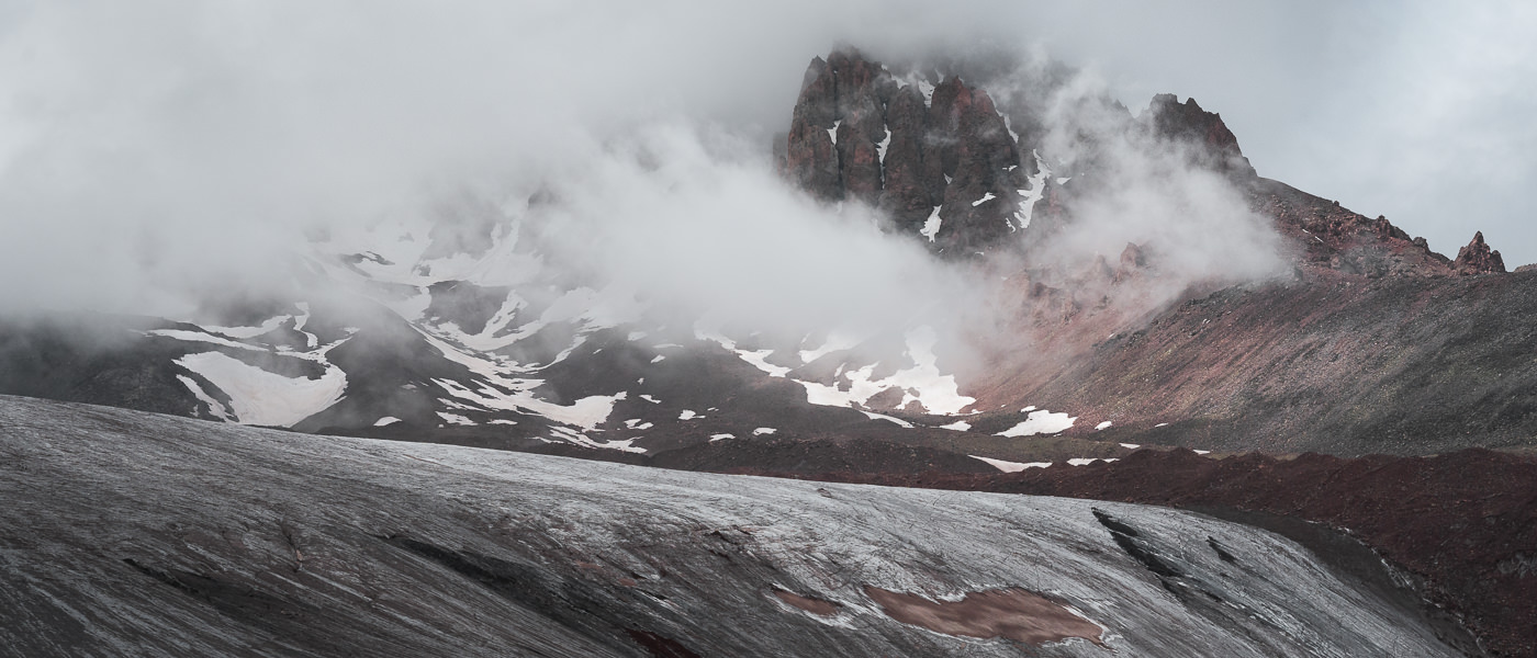 Mist swirls around the mountains above Gergeti Glacier while a shaft of sunlight illuminates some patches of snow