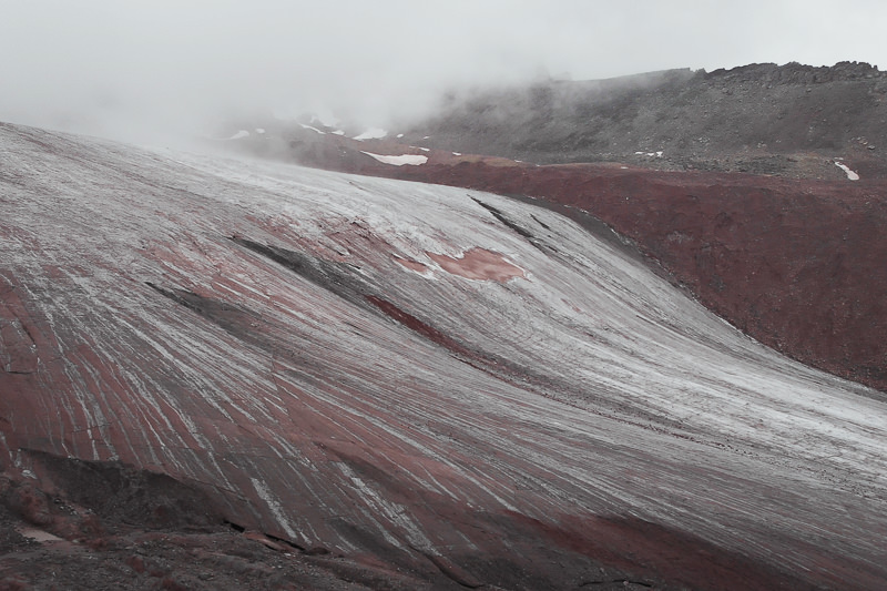 This view of the sloping face of Gergeti Glacier shows the pinky red hue of the rocks and the striations of the glacier