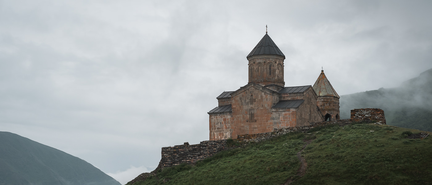 Gergeti Holy Trinity Church surrounded by grey clouds and mist on an overcast morning above Kazbegi in northern Georgia