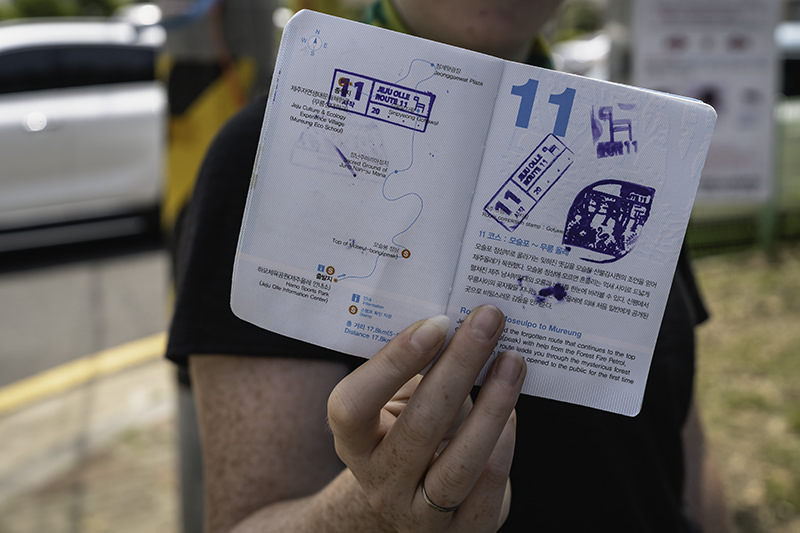 A person displays the stamped pages of their Olle Trail passport outside the Jeju Olle Information Centre in Hamo