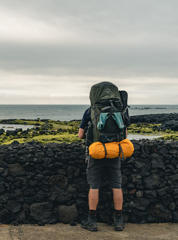 A man wearing a large backpack with yellow tent attached stands by a black volcanic stone rock looking out to sea on Jeju Island, South Korea